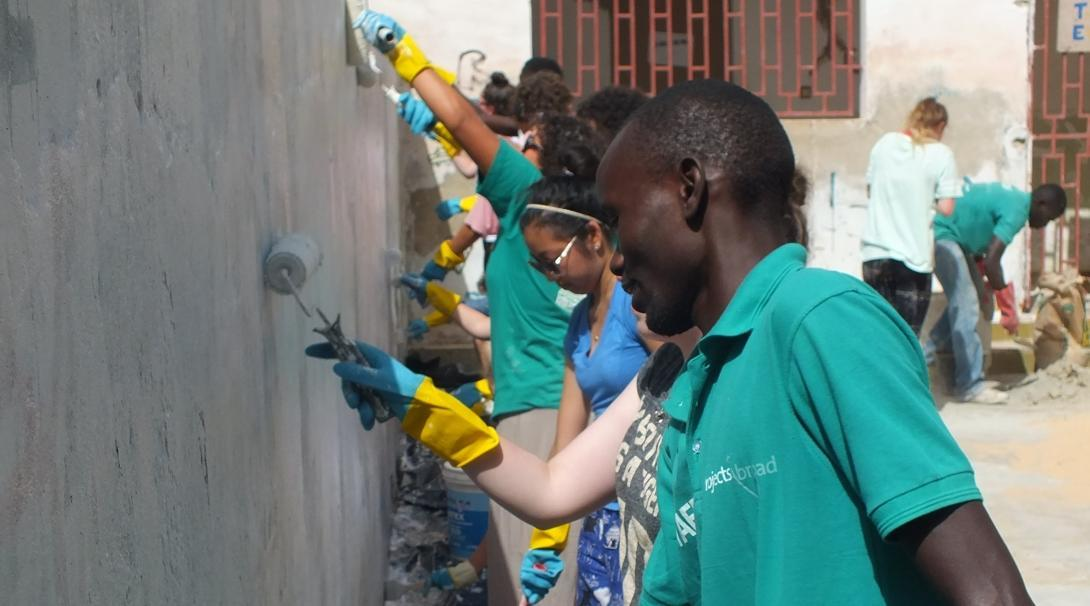 A staff member supports volunteers as they paint a newly constructed wall on one of our volunteer building projects
